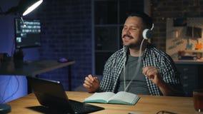 Homme gai dans des écouteurs dansant dans le bureau la nuit ayant l'amusement fonctionnant alors banque de vidéos