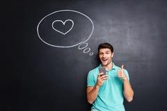 Homme gai dans l'amour utilisant le téléphone portable au-dessus du fond de tableau noir Photographie stock libre de droits