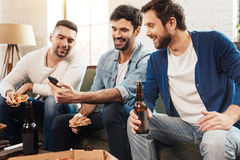 Homme gai de brune tenant son smartphone Image stock