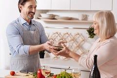 Homme gai faisant cuire la salade avec sa mère dans la cuisine Photographie stock libre de droits