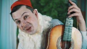 Homme gai habillé en tant que nain barbu jouant la guitare acoustique rotations autour banque de vidéos