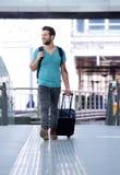 Homme gai marchant avec des sacs à la station de train Photos stock