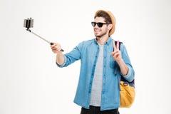 Homme gai prenant des photos avec le téléphone portable et le bâton de selfie Photo libre de droits