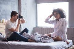 Homme gai prenant la photo de son amie de pose Photo stock
