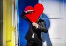 Homme gai se cachant derrière un coeur Image libre de droits