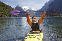 Homme gai supportant l'aviron dans le lac mountain photos libres de droits