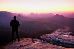 Homme grand dans le noir sur la falaise et la montre au lever de soleil de montagne Silhouette dans la pose pleine d'assurance Photographie stock