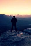 Homme grand dans le noir sur la falaise et la montre au lever de soleil de montagne Silhouette dans la pose pleine d'assurance Photo libre de droits