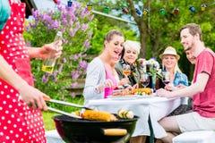 Homme grillant la viande et des légumes sur la réception en plein air Image stock