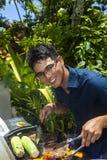 Homme grillant tout entier dans son jardin Photographie stock libre de droits