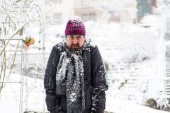 Homme grincheux dans un jardin neigeux photos stock