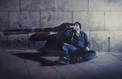 Homme grunge alcoolique s'asseyant sur le maïs moulu de rue photo libre de droits