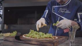 Homme habile dans l'uniforme de cuisinier préparant le plat savoureux enveloppé dans le lavash Main de chef dans la laitue en cao clips vidéos