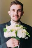 Homme habillé élégant tenant le bouquet des roses blanches d'isolement sur le fond brûlé d'or Images stock