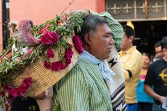 Man dressed with traditional clothes and carrying a basket with flowers and a turkey Little girl dressed with traditional clothes