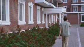 Homme habillé occasionnel marchant sur la rue et parlant par mouvement lent de smartphone clips vidéos