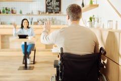 Homme handicapé écartant à son ami dans un café Image libre de droits