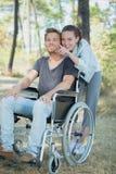 Homme handicapé dans le fauteuil roulant et l'amie dans la forêt Images libres de droits