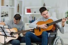 Homme handicapé dans le fauteuil roulant jouant la guitare avec l'ami Images libres de droits