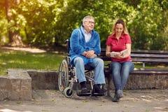 Homme handicapé en parc passant le temps ainsi que sa fille au sujet de Photographie stock
