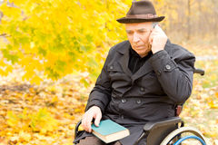 Homme handicapé plus âgé à l'aide d'un téléphone portable Photographie stock libre de droits
