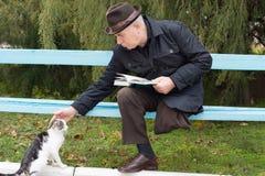 Homme handicapé plus âgé frottant un chat Image stock