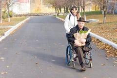 Homme handicapé supérieur avec un soignant féminin Image stock