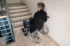 Homme handicapé sur le fauteuil roulant devant l'escalier Image stock
