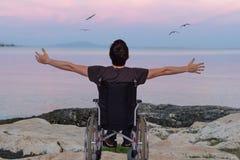 Homme handicapé sur le fauteuil roulant près de la plage au coucher du soleil image libre de droits