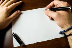 Homme haut étroit de vue écrivant à blanc la table en bois menteuse de papier de stylo-plume stationnaire de pointe Travail de pr images stock
