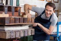 Homme heureux à l'aide de la machine de papier de presse dans l'usine photos libres de droits