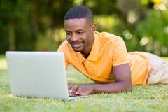Homme heureux à l'aide de son ordinateur portable Photos libres de droits