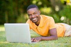 Homme heureux à l'aide de son ordinateur portable Image stock