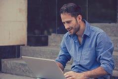 Homme heureux à l'aide de son ordinateur portable souriant dehors Photographie stock libre de droits