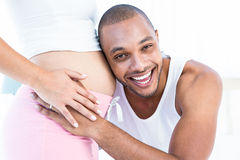 Homme heureux écoutant le ventre de l'épouse enceinte photos stock