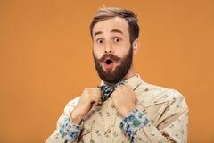 Homme heureux étonné avec la barbe et moustache regardant en longueur dans l'excitation, sur le fond orange images libres de droits