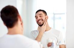 Homme heureux appliquant la lotion après-rasage au miroir de salle de bains Photographie stock libre de droits