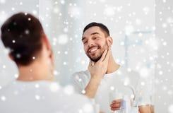 Homme heureux appliquant la lotion après-rasage au miroir de salle de bains Images stock