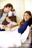 Homme heureux apportant le petit déjeuner dans le lit à l'amie Photos libres de droits