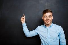 Homme heureux au-dessus de tableau noir point avec un doigt Copyspace Photographie stock