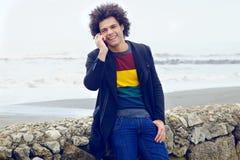 Homme heureux au téléphone avec l'amie devant la plage Photographie stock libre de droits