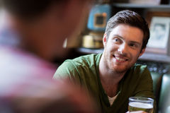 Homme heureux avec de la bière potable d'ami à la barre ou au bar Photo stock
