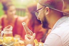 Homme heureux avec des amis de bière à la réception en plein air d'été Photographie stock