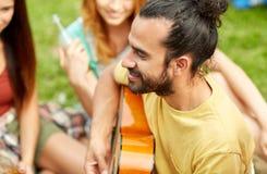 Homme heureux avec des amis jouant la guitare au camping Photo stock