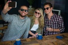 Homme heureux avec des amis prenant le selfie dans le café Image stock