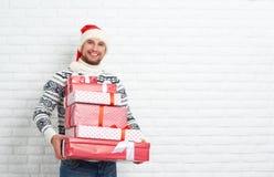 Homme heureux avec des cadeaux de Noël sur le mur vide Photos stock
