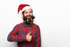 Homme heureux avec des décorations de barbe et de Noël montrant le pouce  Photographie stock