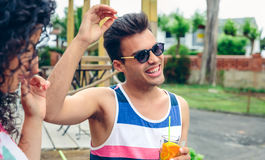 Homme heureux avec des lunettes de soleil riant en partie d'été Images stock