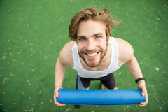 Homme heureux avec le corps musculaire tenant le tapis de yoga ou de forme physique Images libres de droits