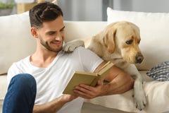 Homme heureux avec le livre et le chien Image libre de droits